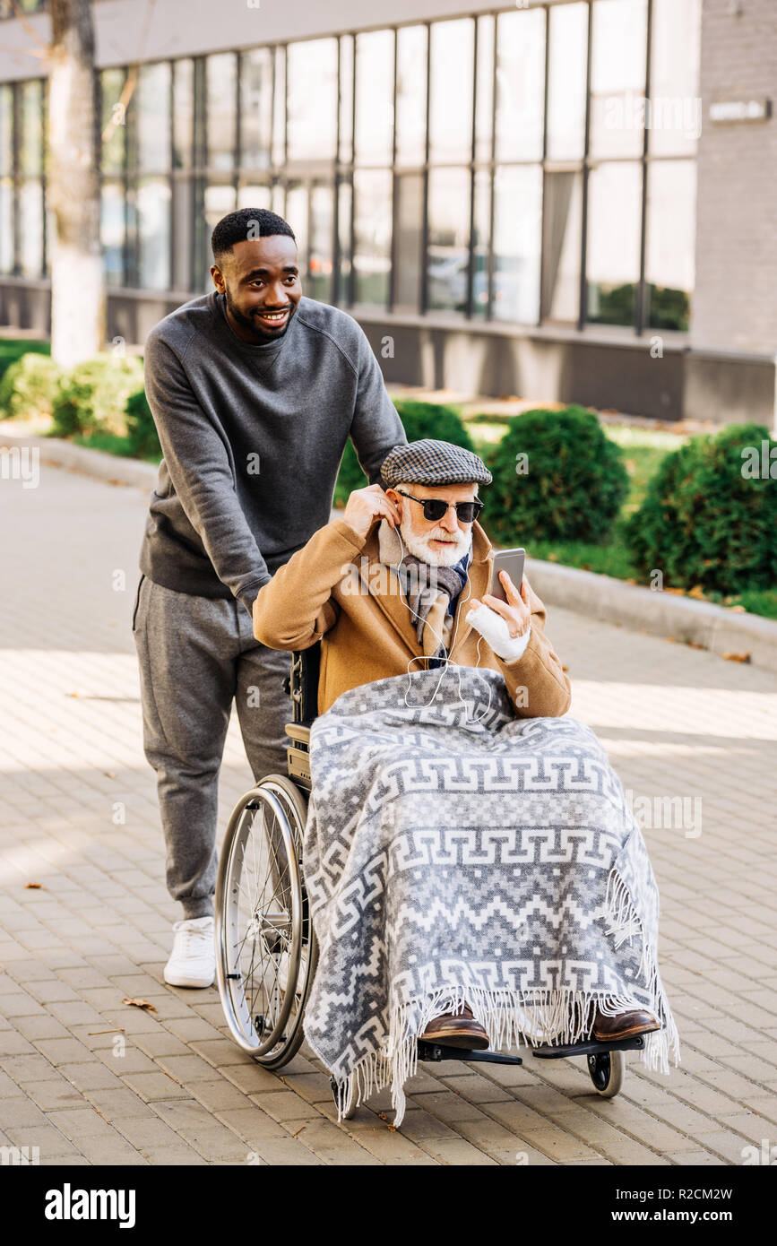 senior disabled man in wheelchair listening musing with smartphone and earphones with african american cuidador on street - Stock Image