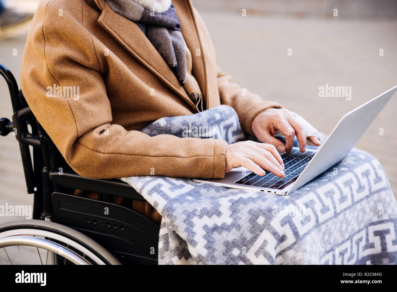 cropped shot of disabled man in wheelchair using laptop on street Stock Photo