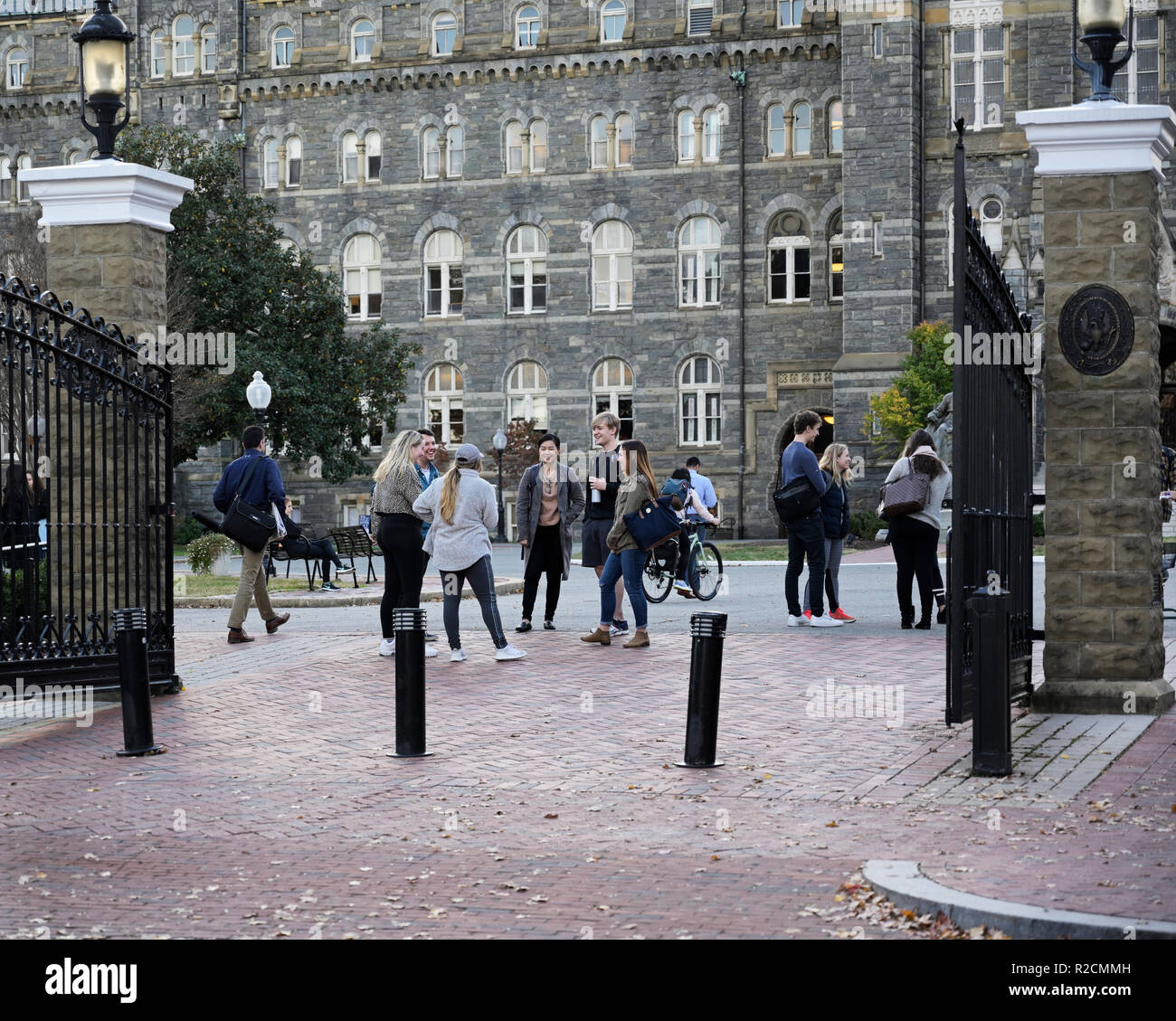 Georgetown University entrance gate with college students talking laughing - Stock Image