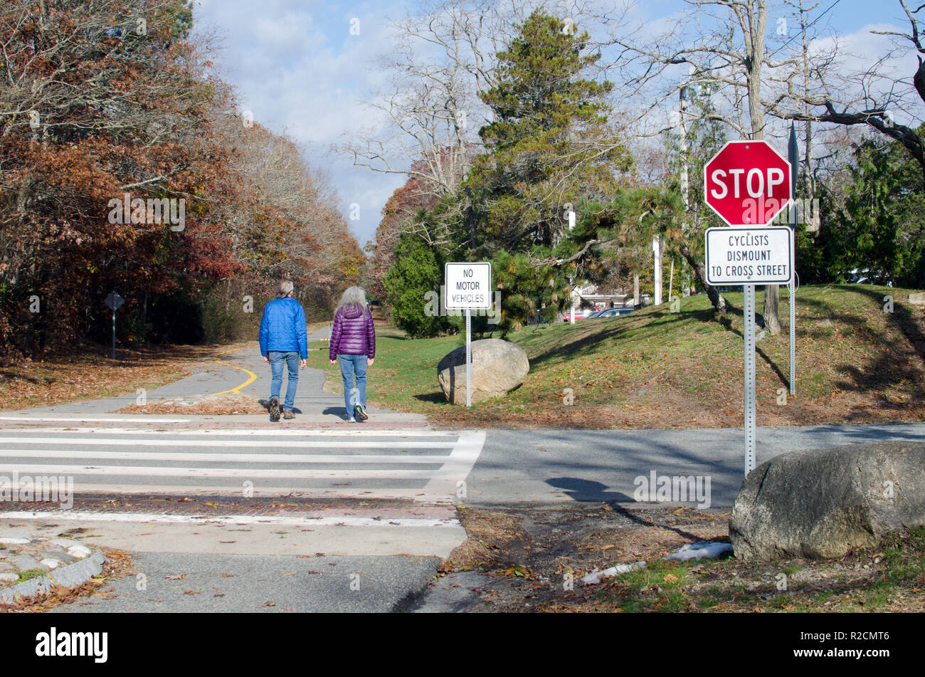 Couple walking on Shining Sea Bikeway  in Falmouth, Cape Cod at road crossing with Cyclists Dismount to Cross Street, No Motor Vehicles & Stop signs - Stock Image