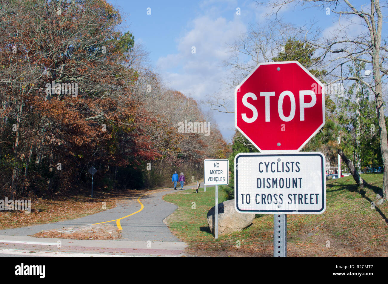Shining Sea Bikeway sign with Stop sign, No Motor Vehicles sign and Cyclists Dismount to Cross Street in Falmouth, Cape Cod, Massachusetts USA - Stock Image