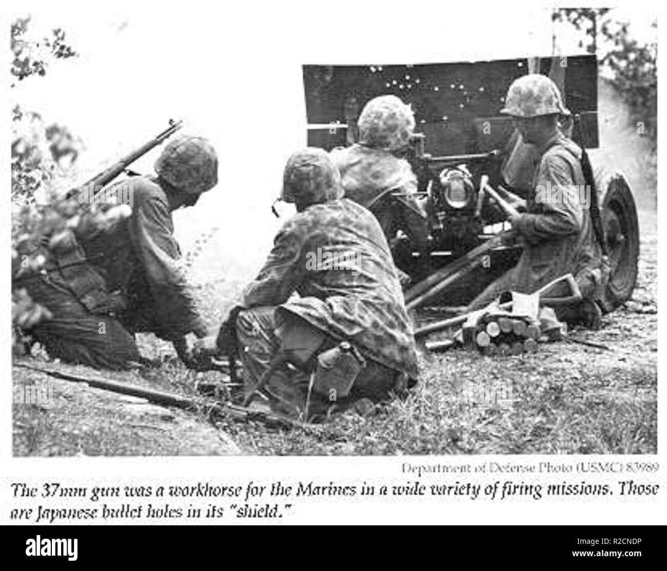 U.S. 37 mm gun crew in action, Saipan, 1944. From left to right are two ammunition carriers, gunner and assistant gunner. Note extended shield. Stock Photo