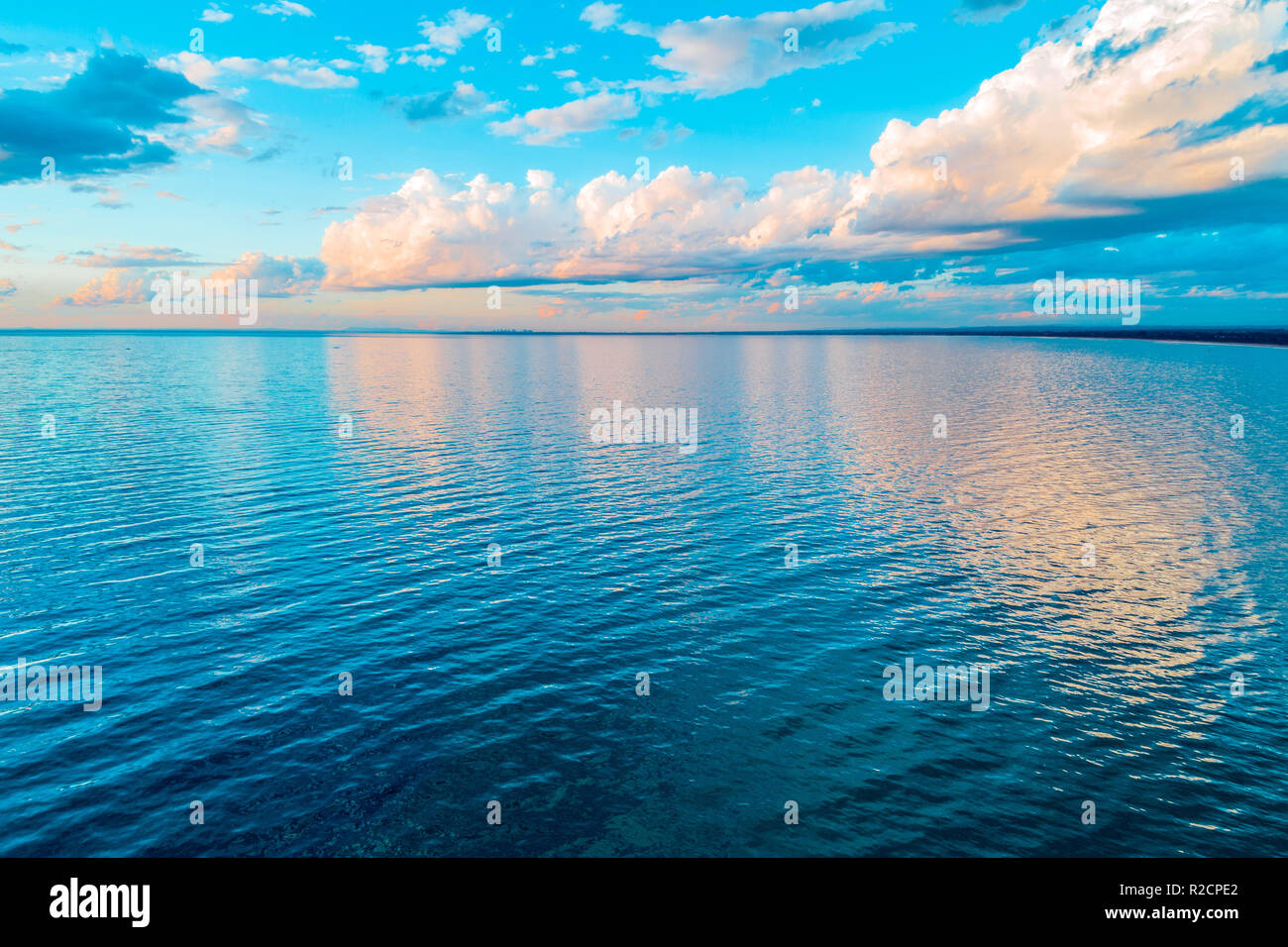 Beautiful minimalism - clouds over calm sea water at sunrise - Stock Image