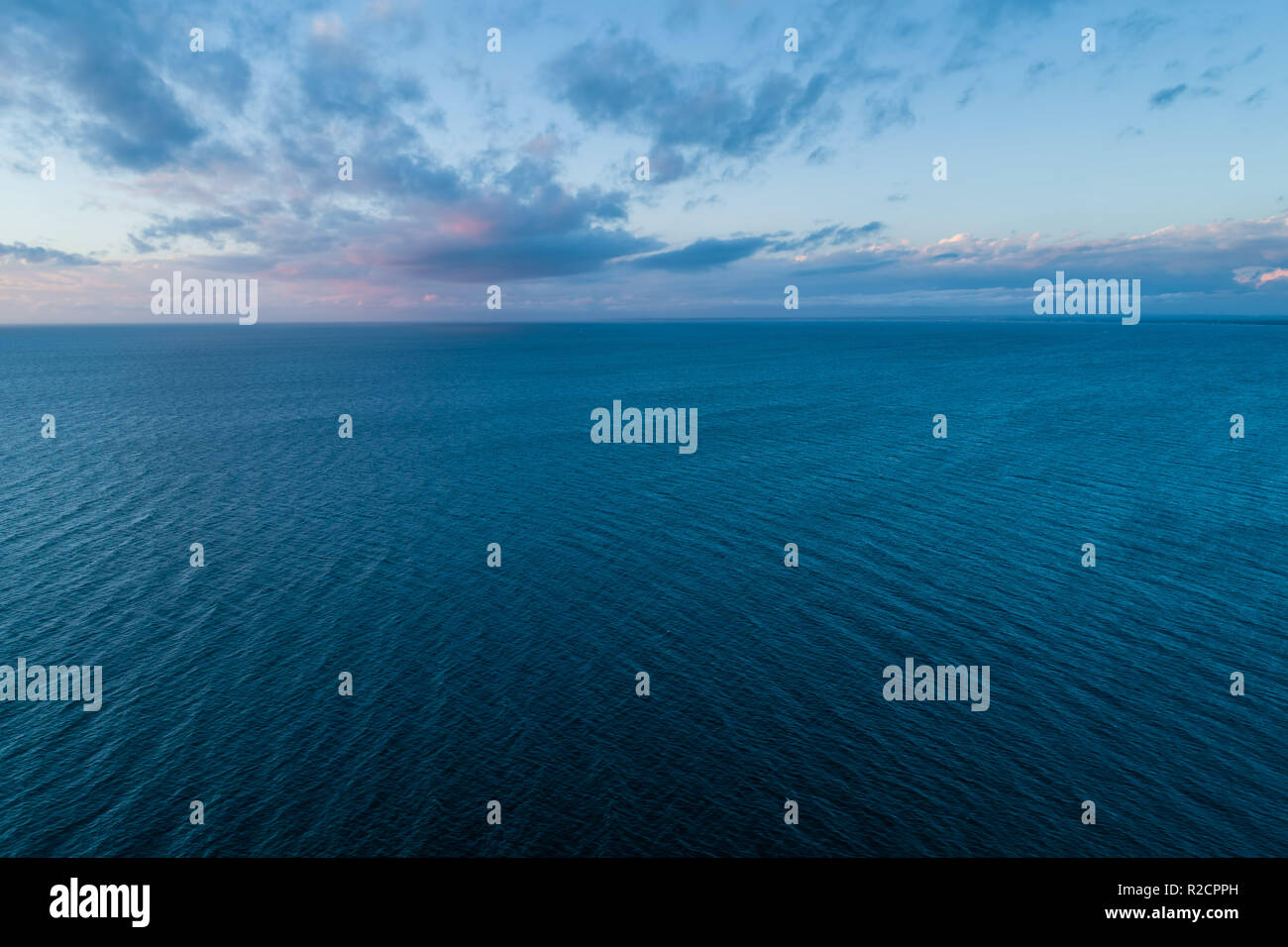 Minimalistic seascape - clouds over water at dusk - Stock Image