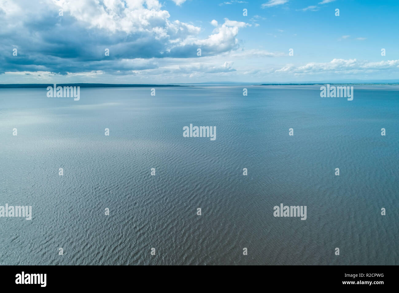 Minimalist landscape of water ripples and white clouds - Stock Image