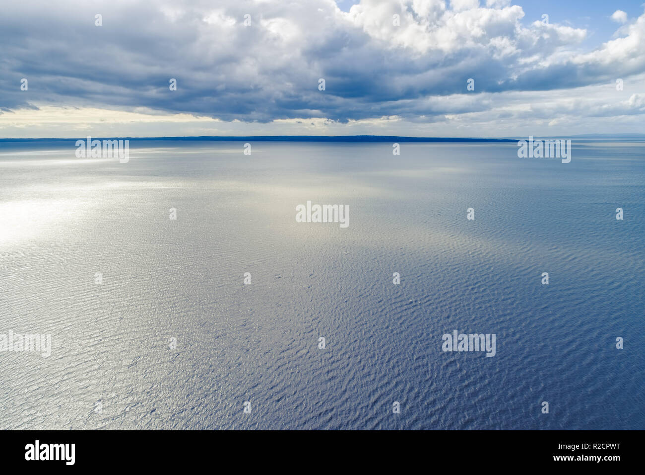 Small patch of land on the horizon with clouds over water - aerial landscape - Stock Image