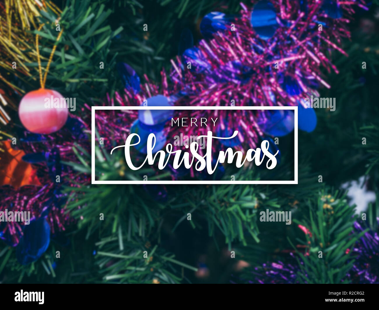 Typographical Merry Christmas Banner. Colorful Christmas background with blurred Christmas ornament prop decoration on Christmas tree background. - Stock Image