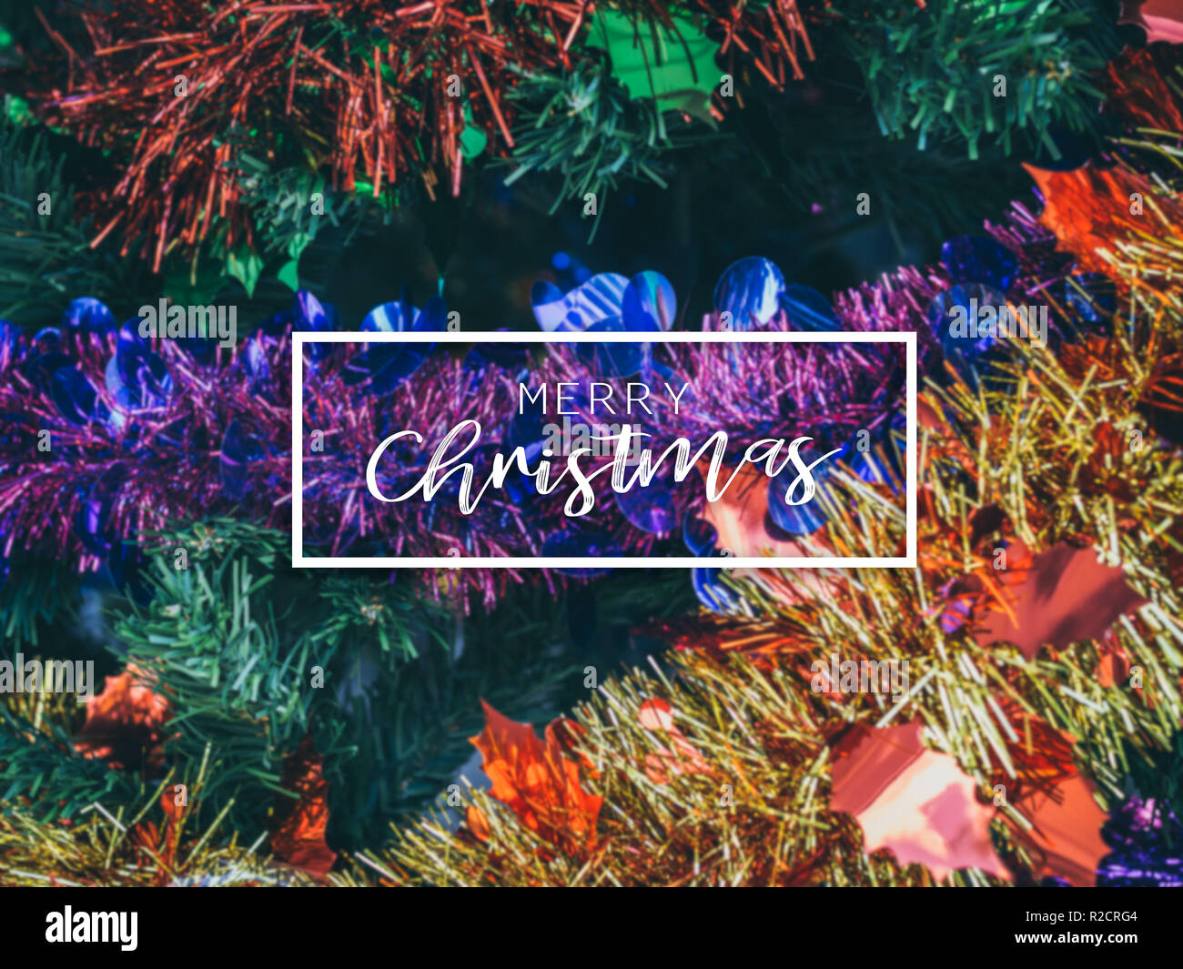 Typographical Merry Christmas Banner. Colorful Christmas background with Christmas ornament prop decoration on Christmas tree. - Stock Image