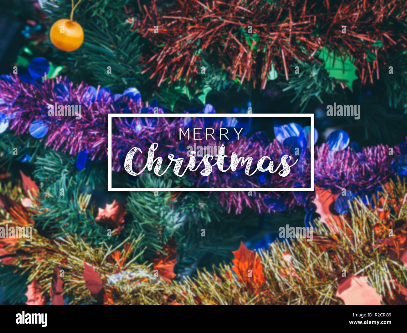 Typographical Merry Christmas Banner. Colorful Christmas background with Christmas ornament prop decoration on Christmas tree background. - Stock Image