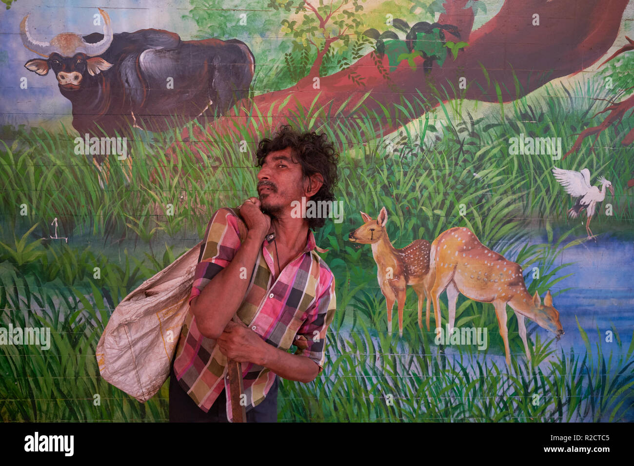 A beggar, originally from Assam, India, crippled and deformed through a traffic accident, passing a wall painting in Byculla Station in Mumbai, India - Stock Image