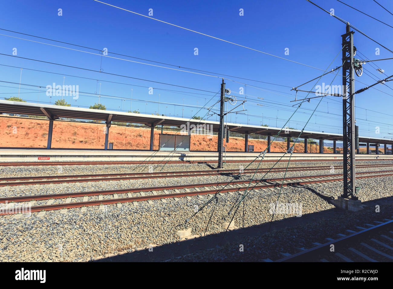 Train tracks with overhead catenary and electric lines in a blue sky background, at Cuenca station Stock Photo