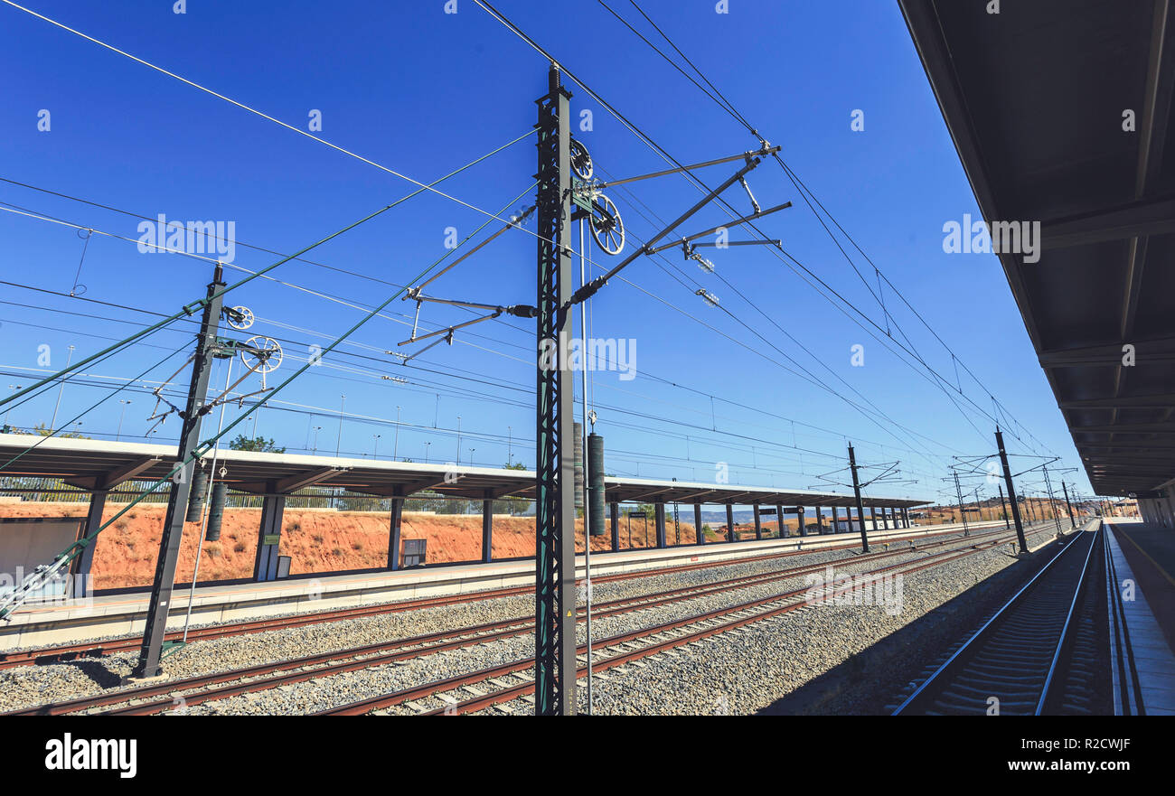 Train tracks with overhead catenary and electric lines in a blue sky morning, at Cuenca station Stock Photo