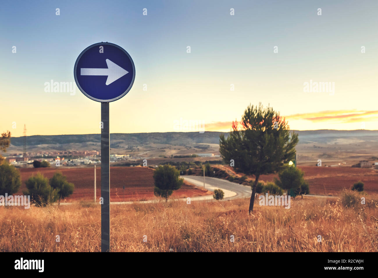 Mandatory direction traffic sign to the right at sunrise with blue sky background - Stock Image