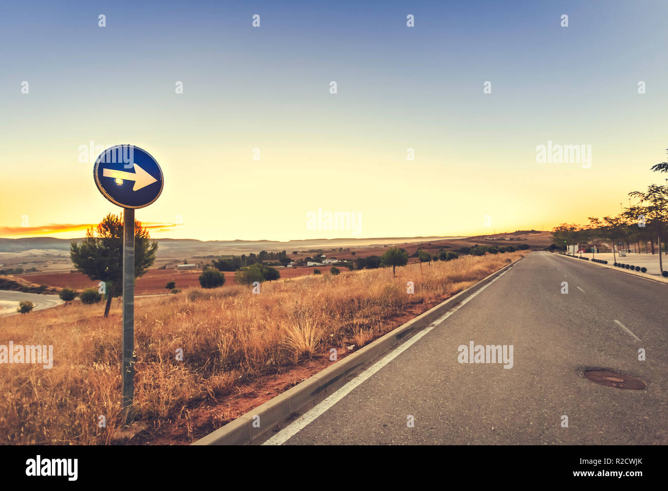 Mandatory direction traffic sign to the right with highway at sunrise and blue sky background - Stock Image