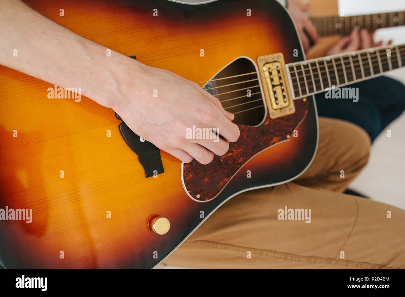 Learning to play the guitar. Interesting hobby or professional occupation of music. Music education or extracurricular activities or pastime - Stock Image