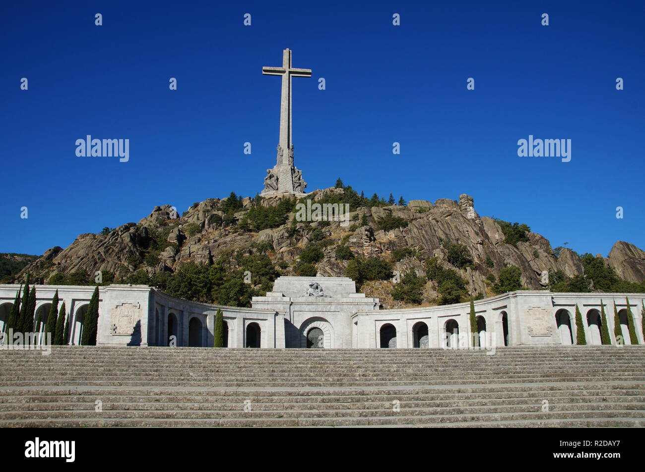 04 October 2018, Spain, El Escorial: A 155 meter high and 44 meter wide concrete cross stands on the mountain peak Risco de la Nava in the Valle de los Caídos (Valley of the Fallen) about 60 kilometers northwest of Madrid. In the monument in the Sierra de Guadarrama is the tomb of the Spanish dictator Franco. Three days after his death, he was buried in the Basilica on 23 November 1975. The mausoleum, which was driven into the rock by 20,000 forced laborers between 1940 and 1959, is considered one of the largest in the world. It is the most important architectural symbol of Franco's dictators Stock Photo