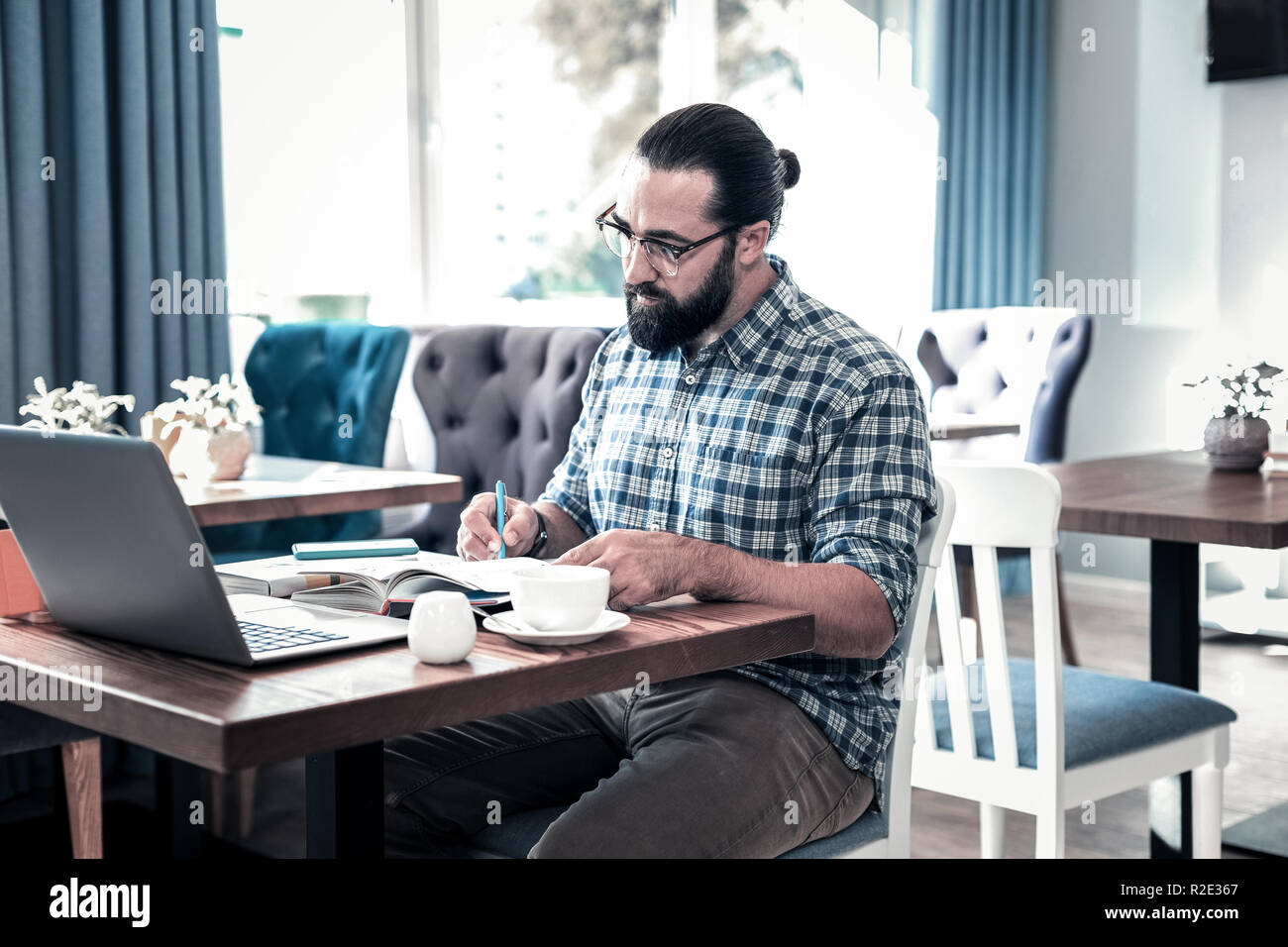 Prosperous professional journalist working hard making some notes - Stock Image