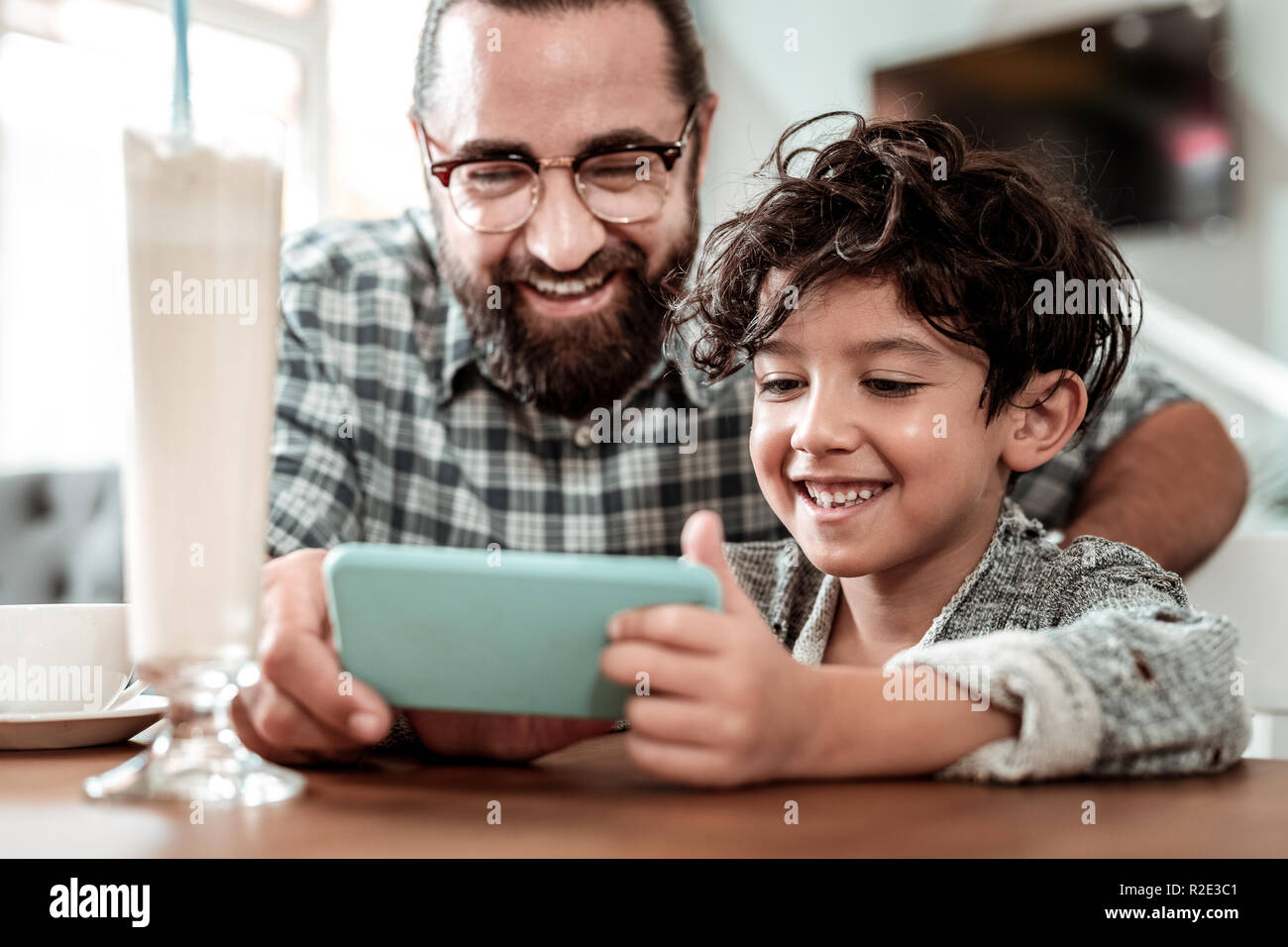Cute smiling handsome son playing online games sitting near