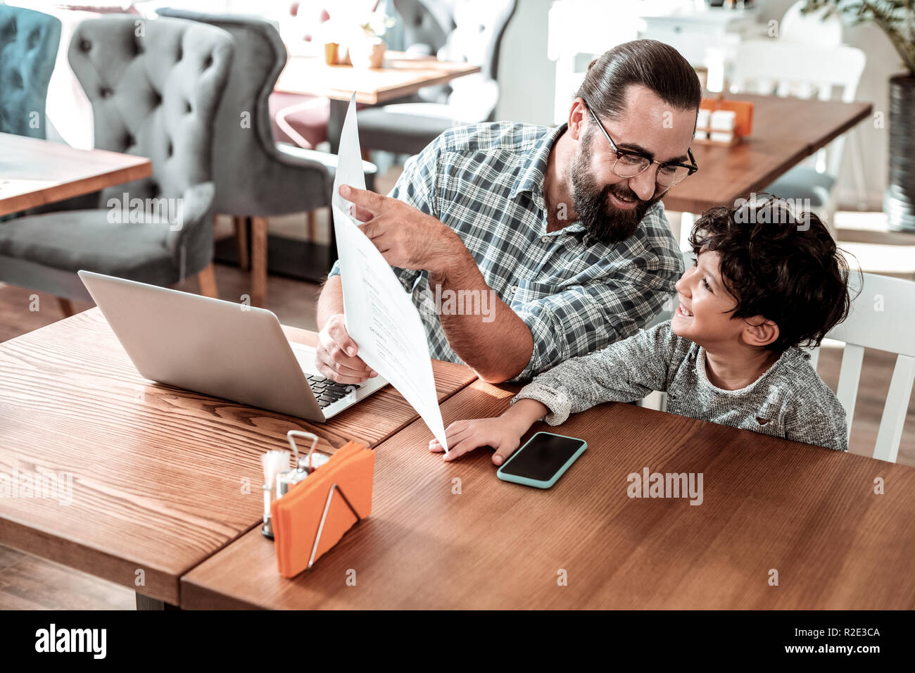 Bearded father recommending some dishes his little son - Stock Image