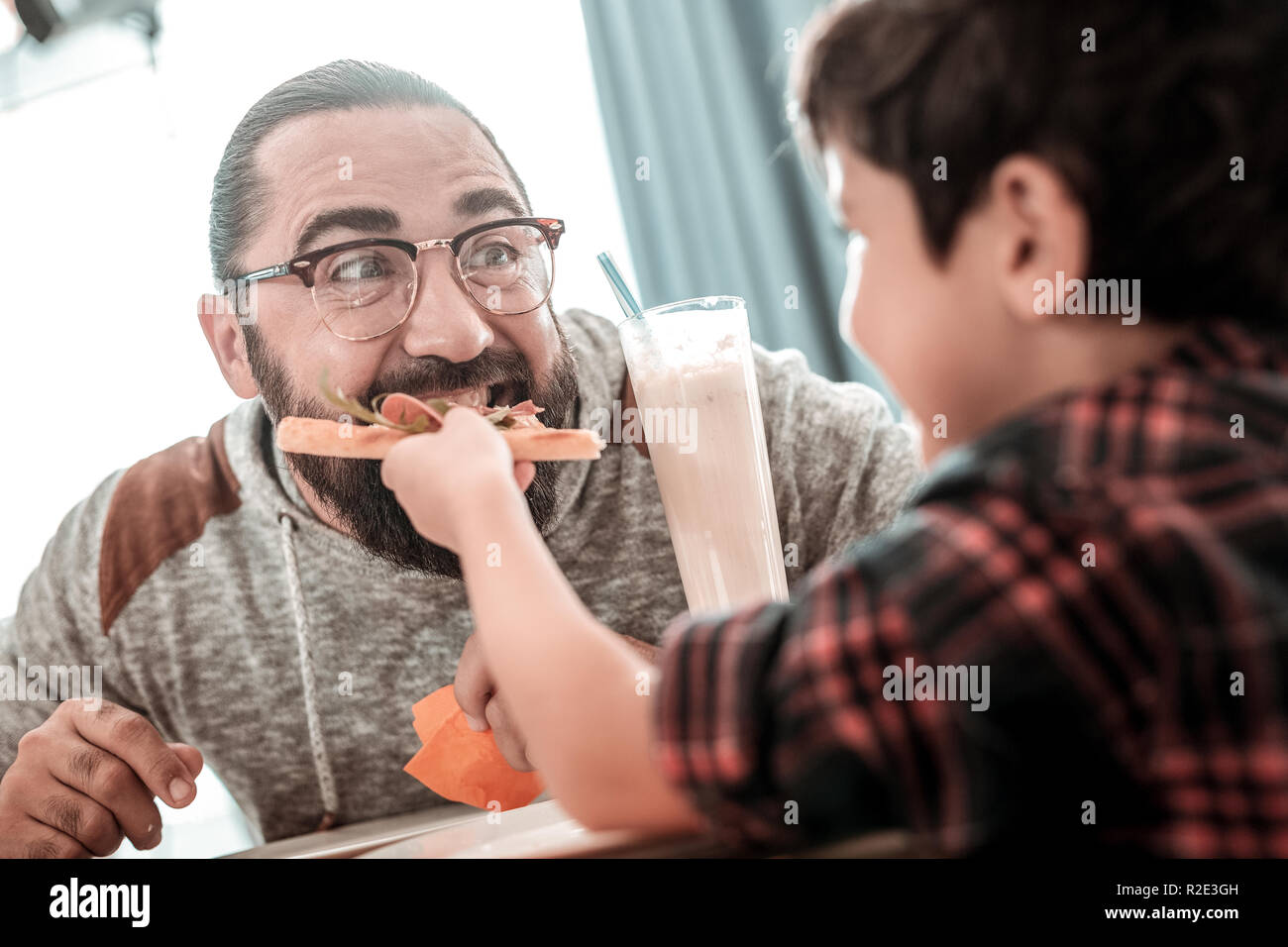 Cute generous son giving piece of pizza to his father - Stock Image