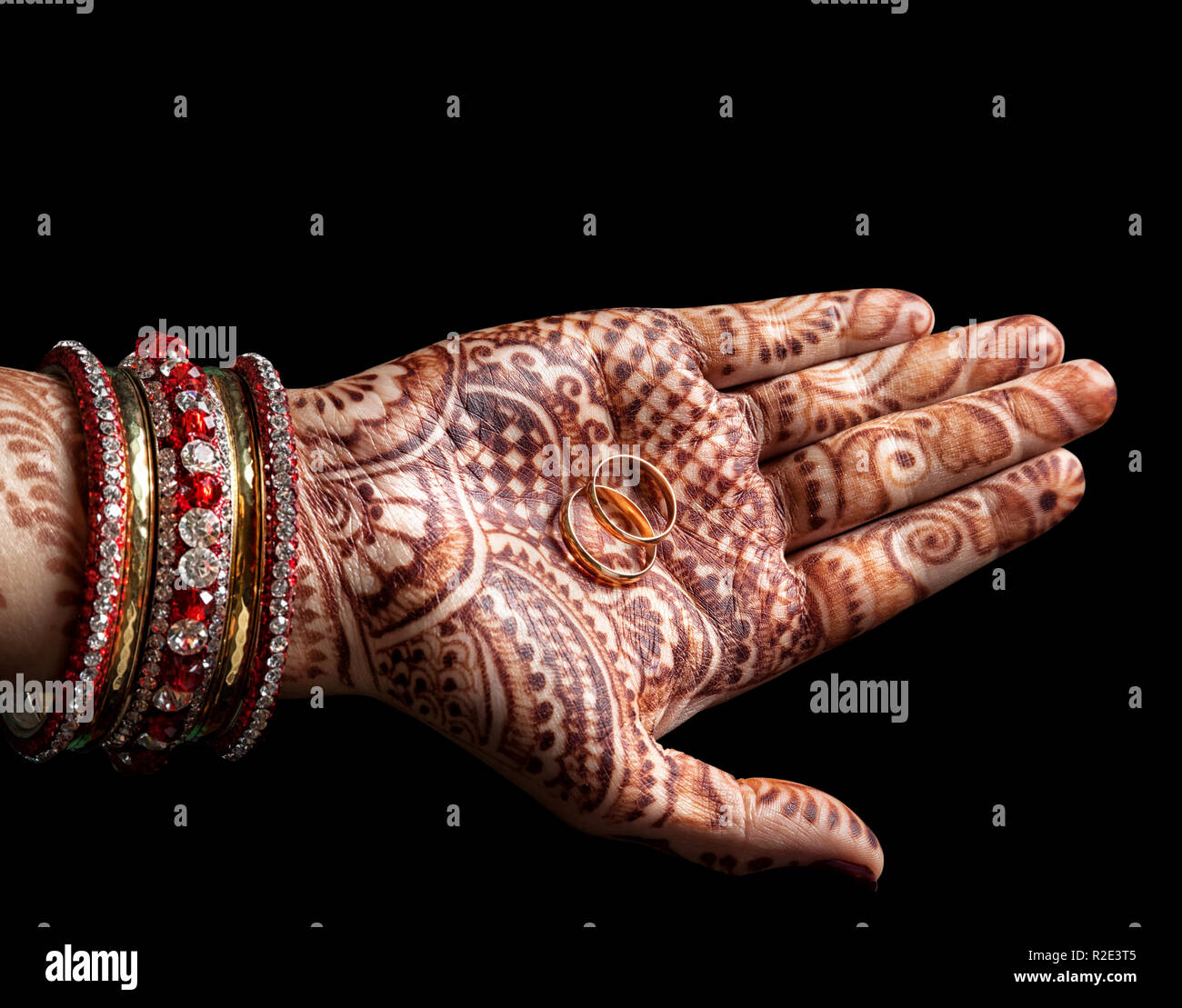 Wedding rings in Woman palm with henna painting on black background - Stock Image