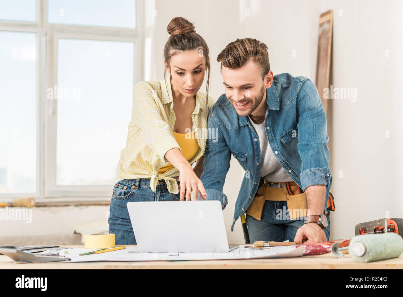 young couple using laptop during home improvement Stock Photo