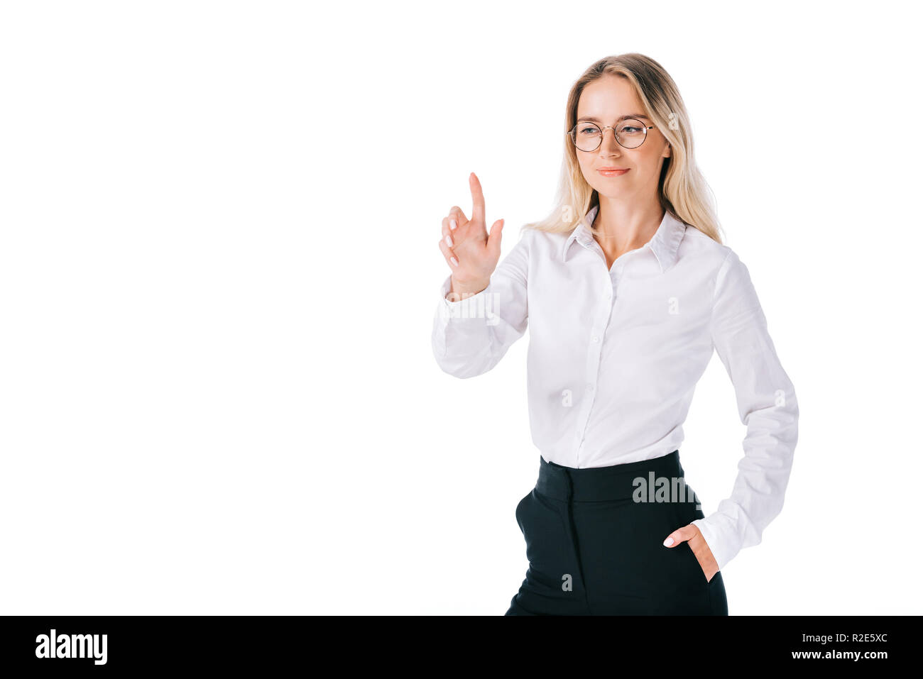 portrait of smiling businesswoman in formal wear gesturing isolated on white - Stock Image