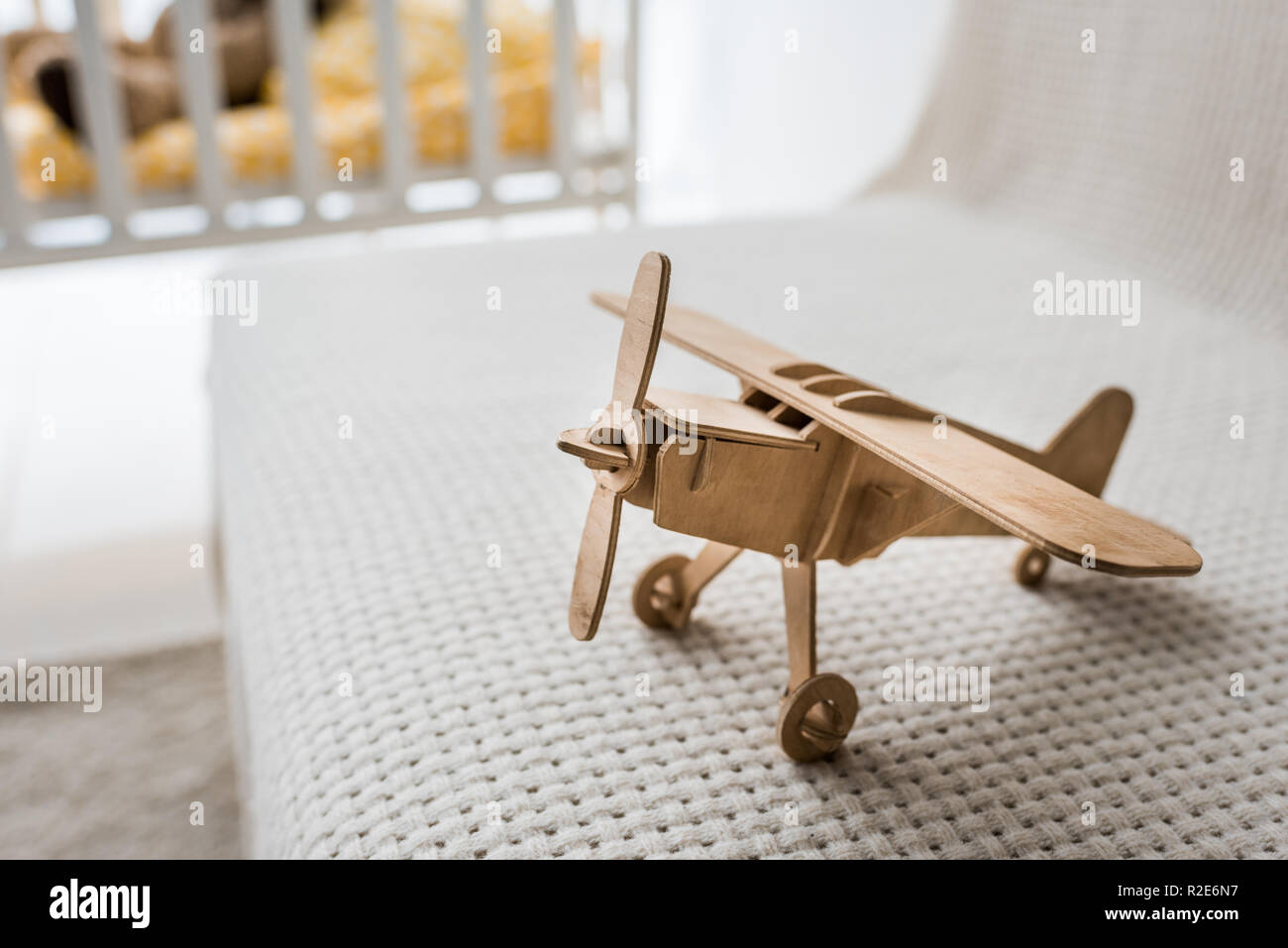 retro wooden toy plane on sofa in nursery room - Stock Image
