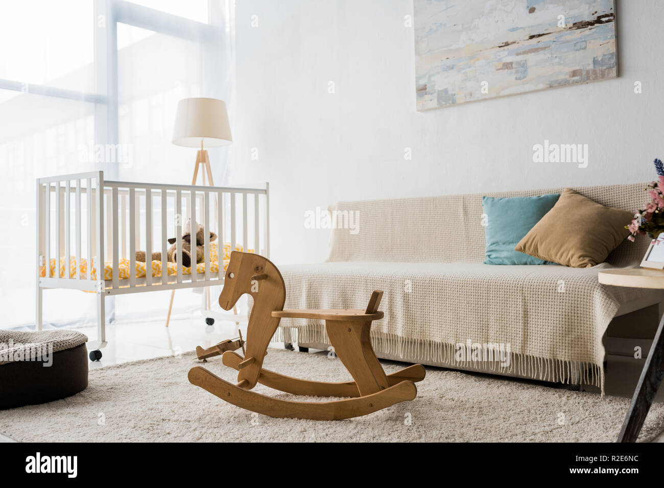 modern interior design of nursery room with crib and rocking horse chair - Stock Image