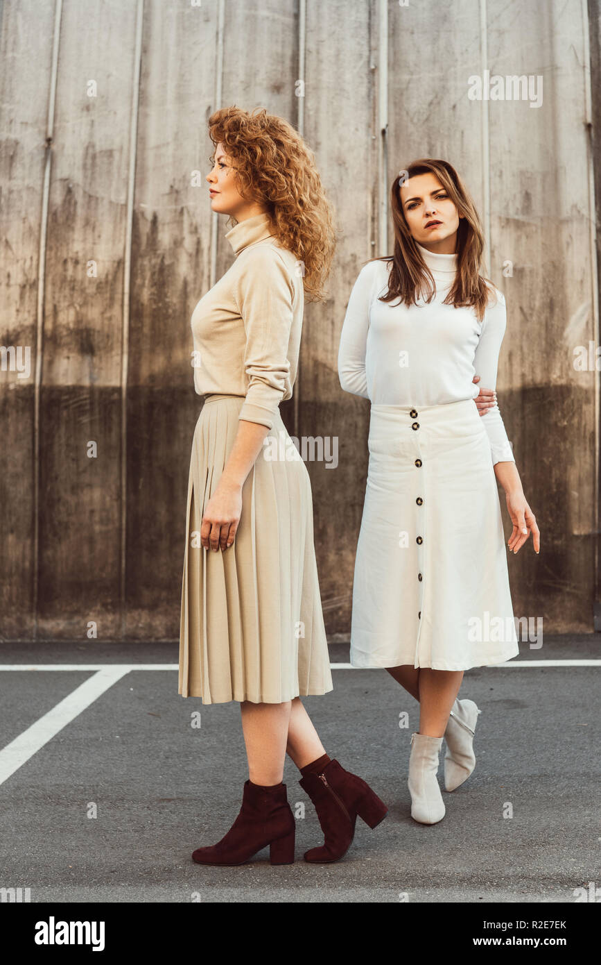 fashionable female models in turtle necks and skirts posing at urban street - Stock Image