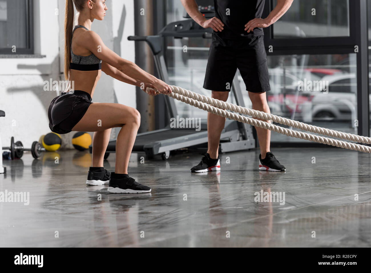 cropped image of trainer watching at athletic bodybuilder working out with ropes in gym - Stock Image