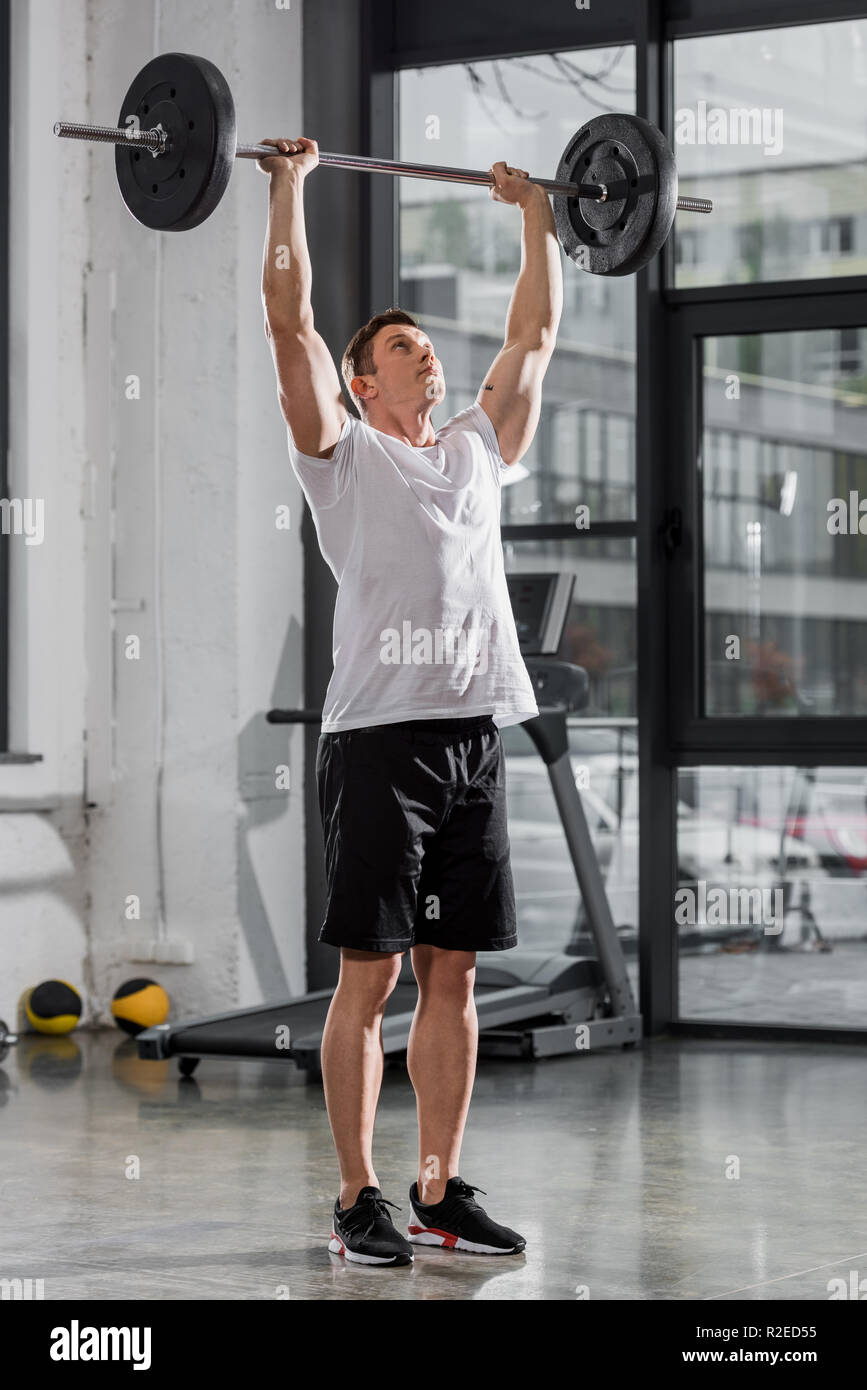 sportive athletic bodybuilder training with barbell in gym Stock Photo