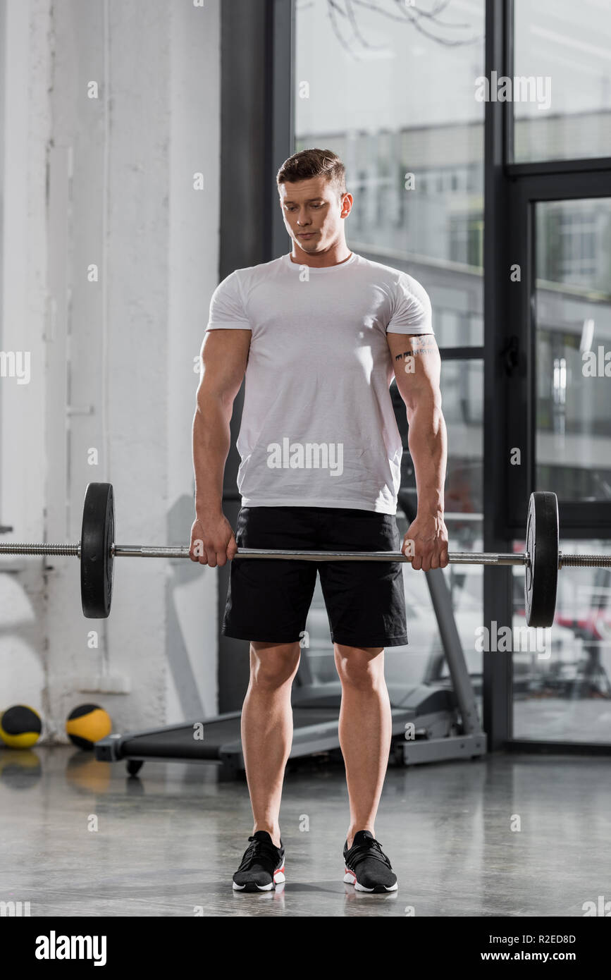 handsome athletic bodybuilder training with barbell in gym Stock Photo