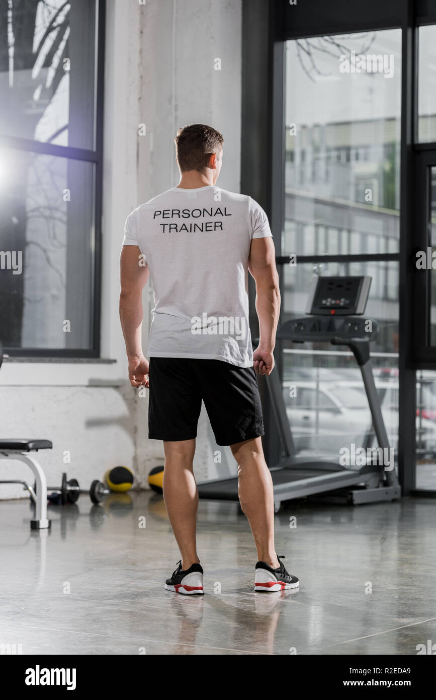 back view of athletic bodybuilder in shirt with text personal trainer standing in gym - Stock Image