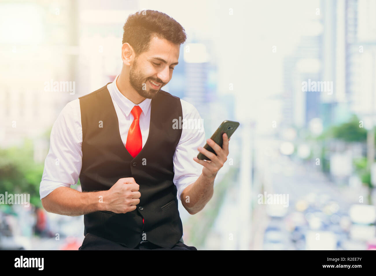 business succeeding or good news from smartphone to latin businessman watching screen - Stock Image