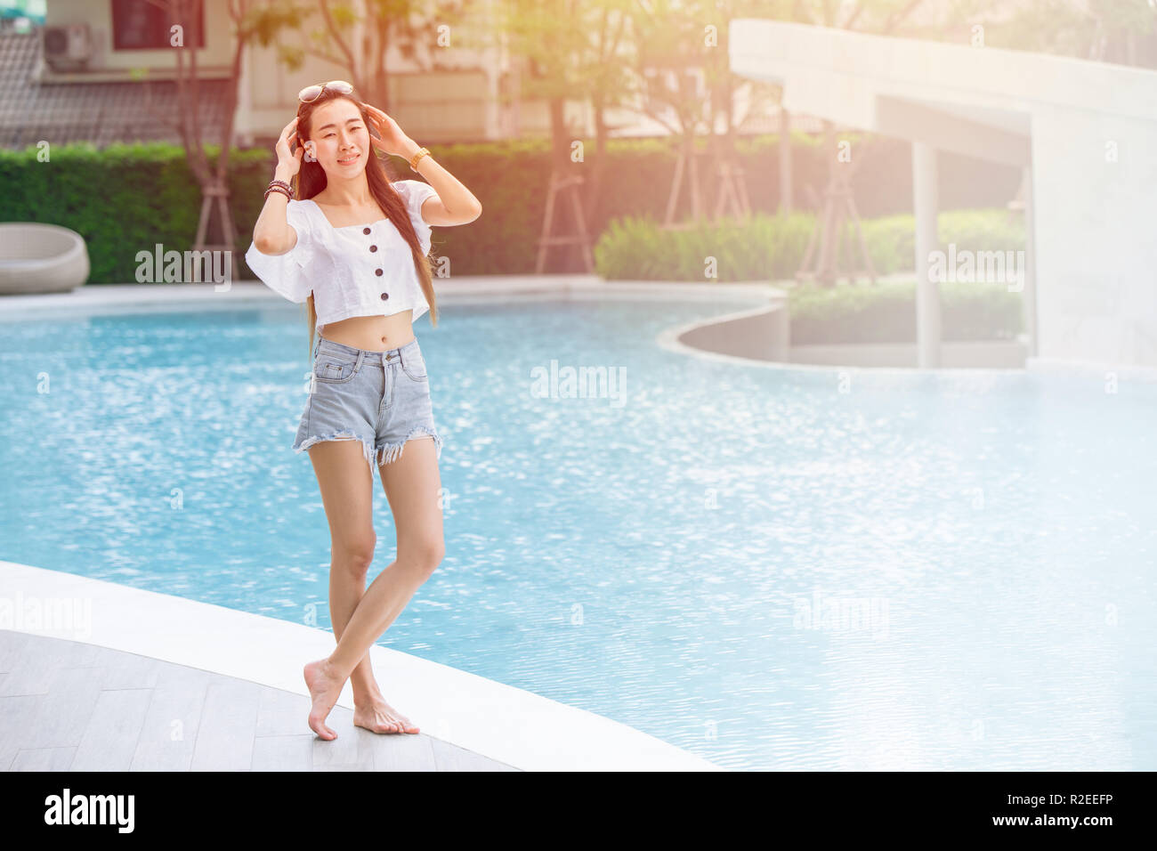 skinny asian girl teen relax smile standing at swimming pool holiday  lifestyle. - Stock Image