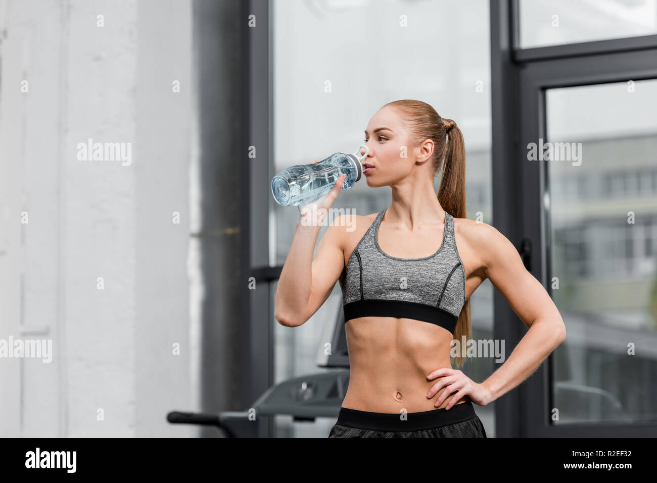 attractive athletic sportswoman drinking water in gym Stock Photo