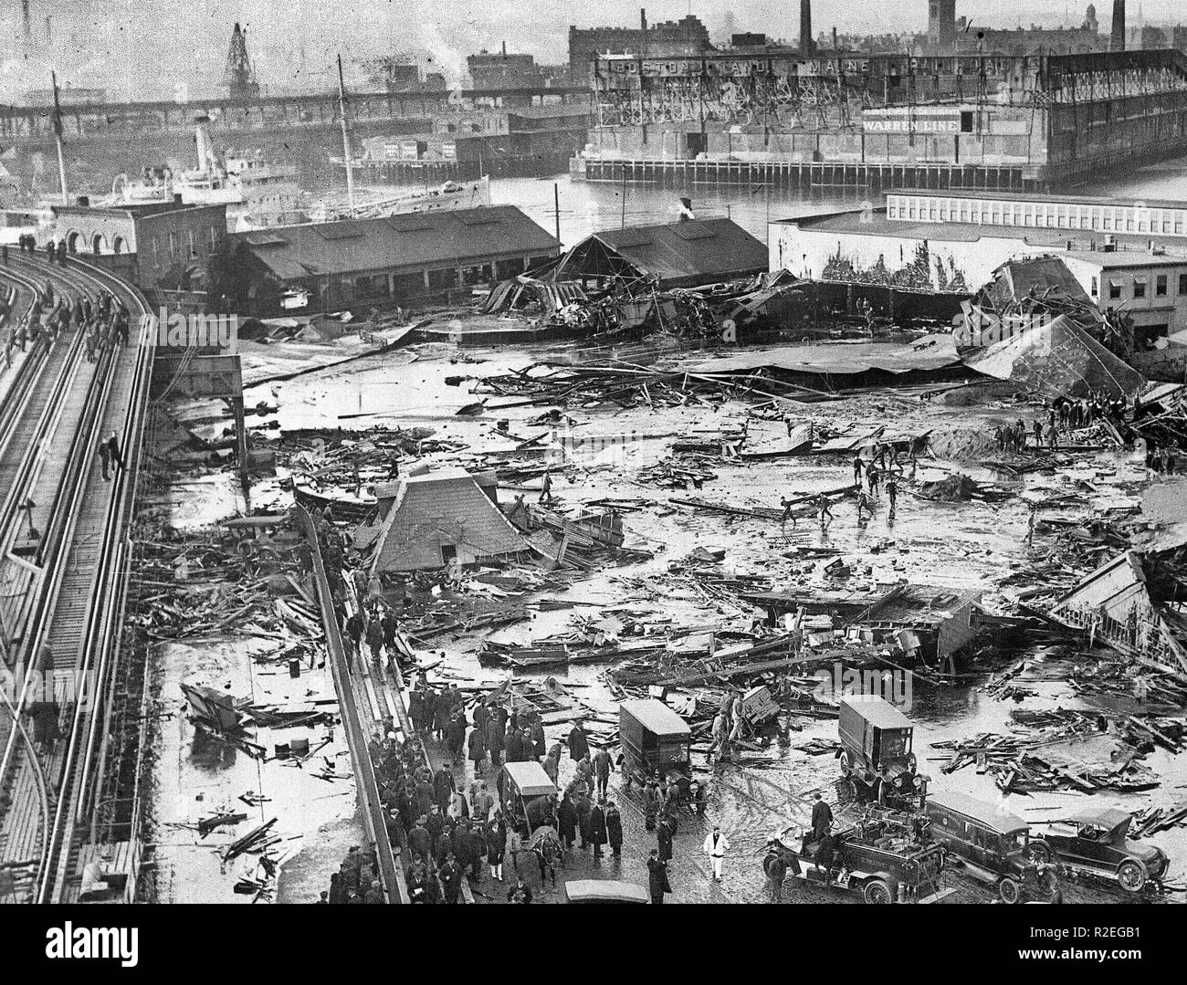 Panorama of the Molasses Disaster site - Twenty one people were killed on Commercial Street in the North End when a tank of molasses ruptured and exploded. An eight foot wave of the syrupy brown liquid moved down Commercial Street at a speed of 35mph. Wreckage of the collapsed tank visible in background, center, next to light colored warehouse. Elevated railway structure visible at far left and the North End Park bathing beach to the far right. January 15, 1919 - Stock Image