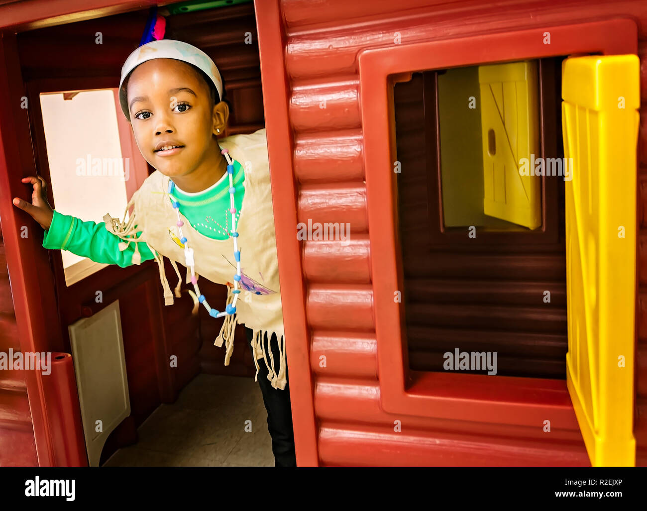 A pre-school student peeks out of a log cabin playhouse while dressed in a Native American Indian costume, Nov. 21, 2012, in Columbus, Mississippi. - Stock Image