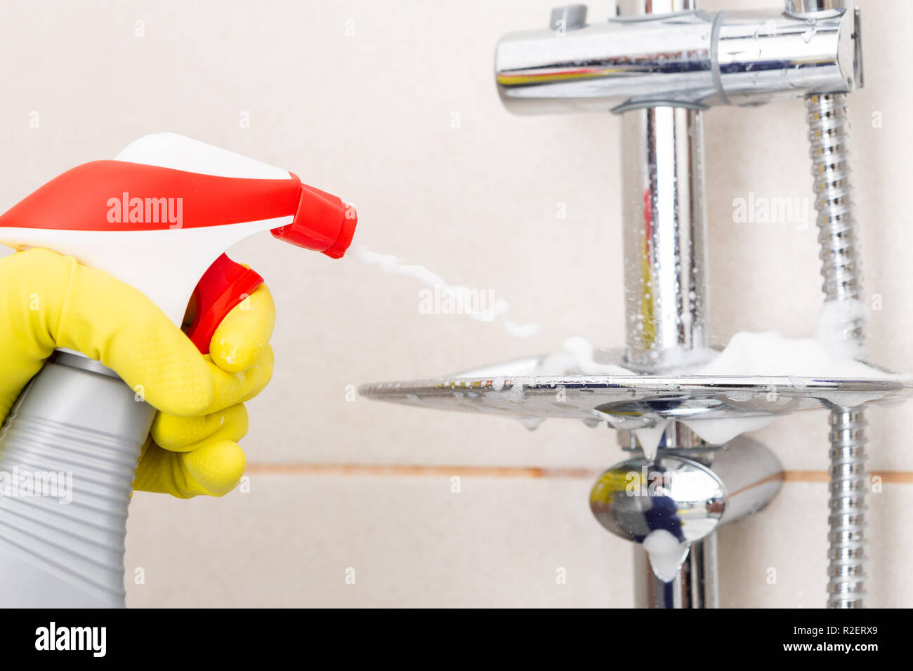 Person wearing rubber hygienic gloves spraying soap holder in shower as chores concept - Stock Image