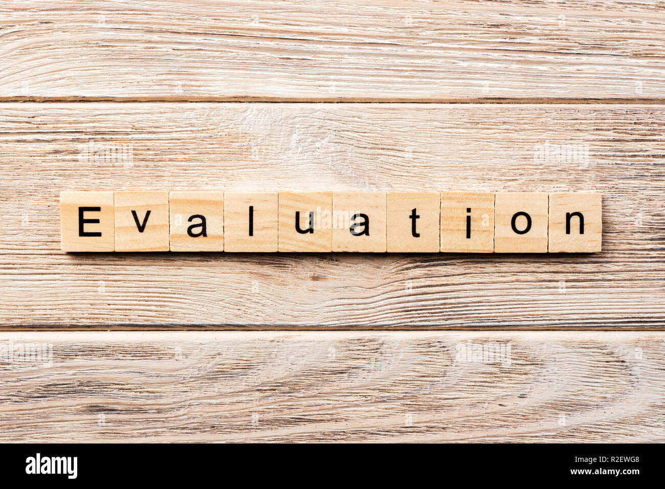 evaluation word written on wood block. evaluation text on table, concept. - Stock Image