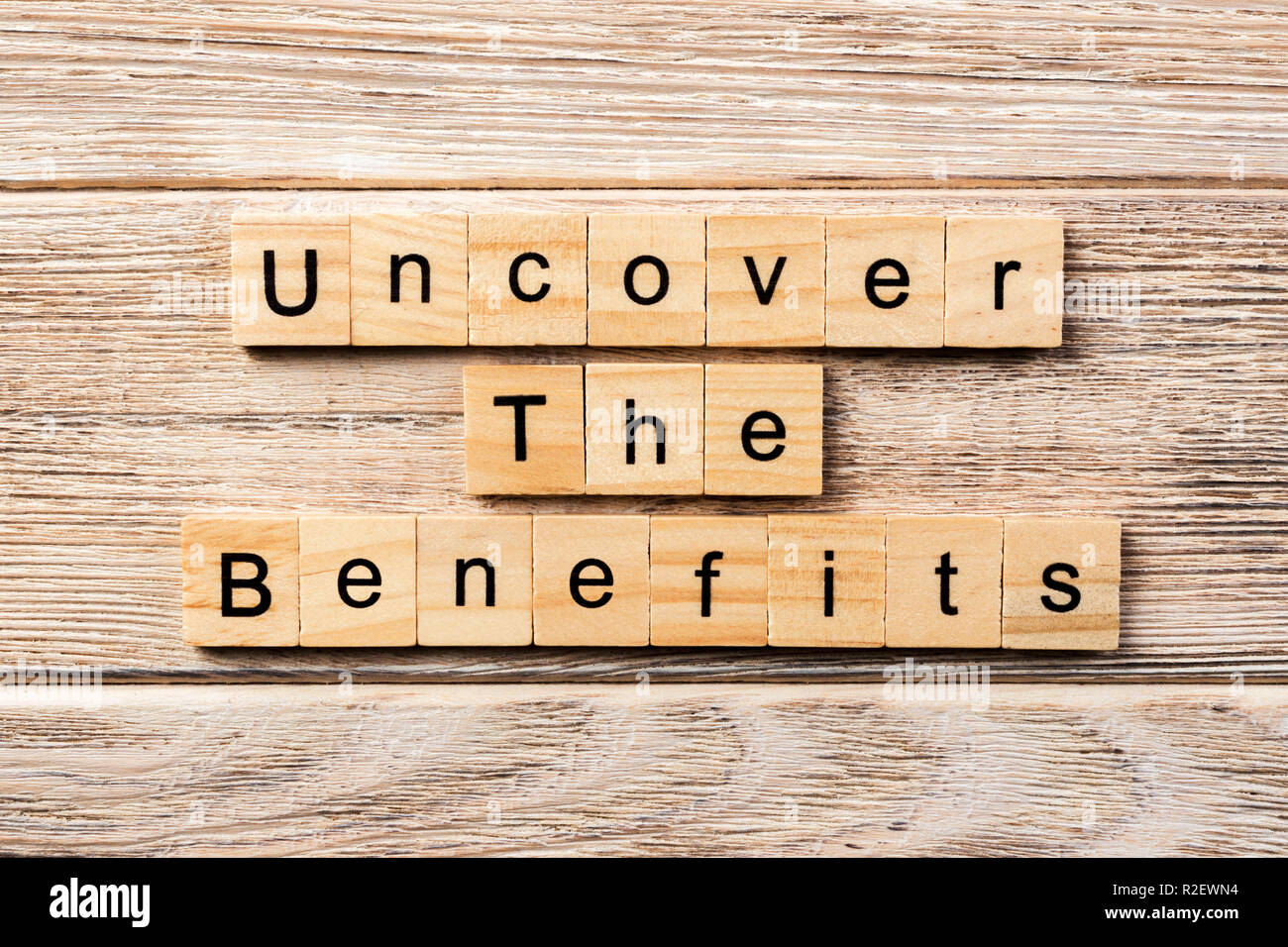 uncover the benefits word written on wood block. uncover the benefits text on table, concept. - Stock Image