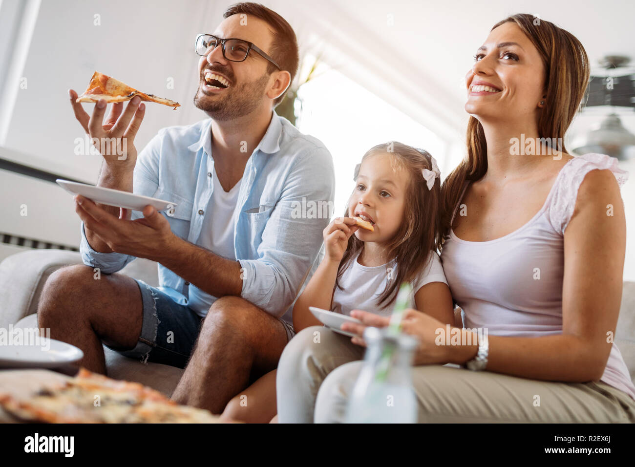 Portrait of happy family sharing pizza at home - Stock Image