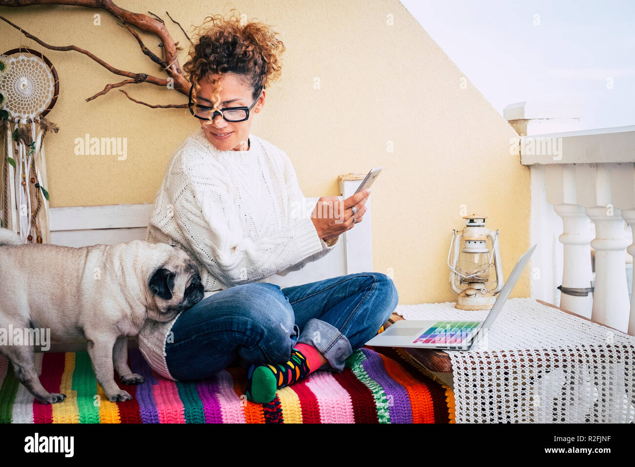 Happy alternative young cheerful woman warking at home with a new business way. sitting on a bench outdoor at home with best friend old pug together. colorful bench and lifestyle. laptop and phone to communicate and internet - Stock Image