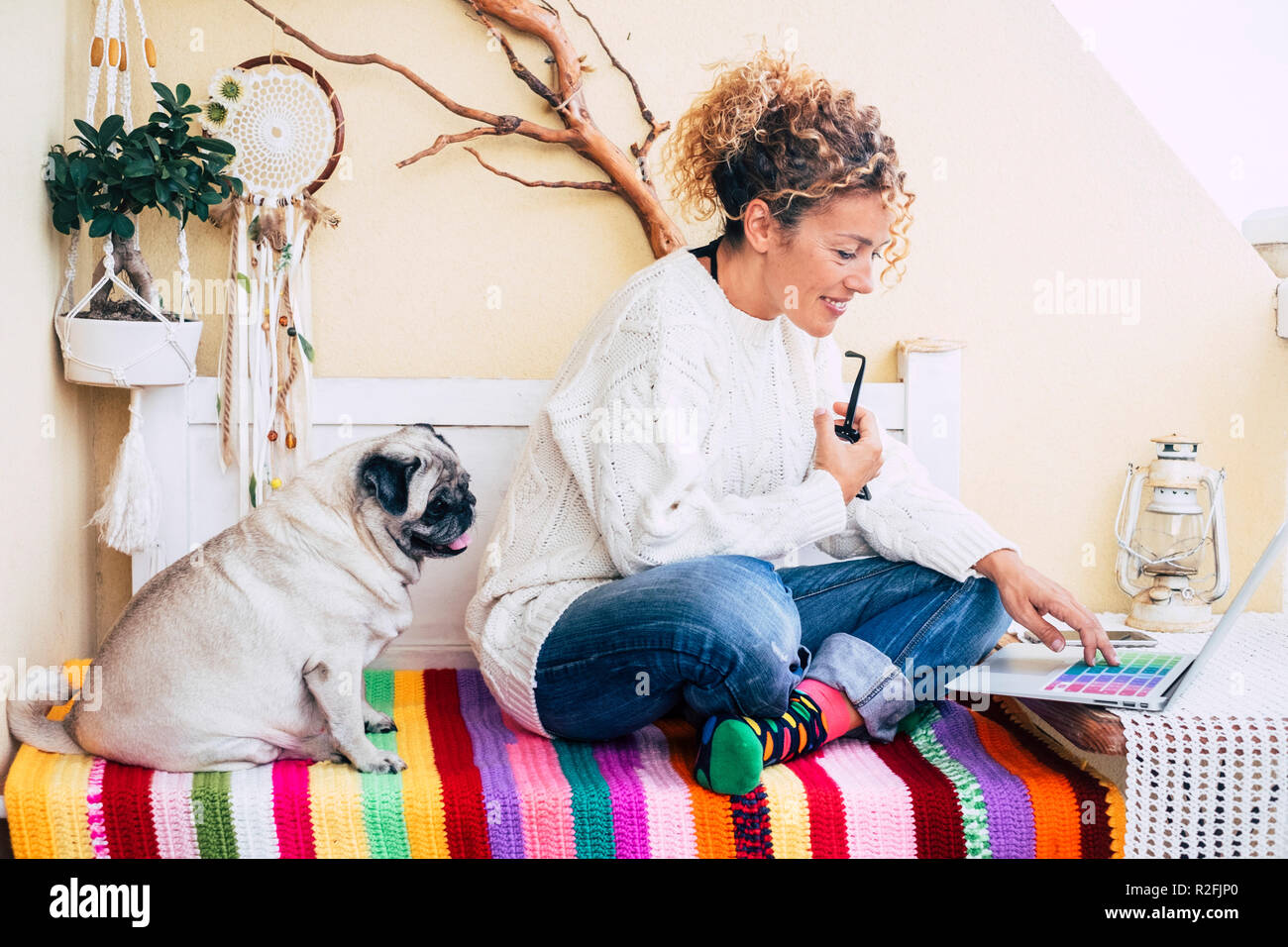 beutiful caucasian woman and funny old pug dog sitting on a bench in the terrace at home working or doing online shopping with a laptop together. friendship and alternative office location concept for free people Stock Photo