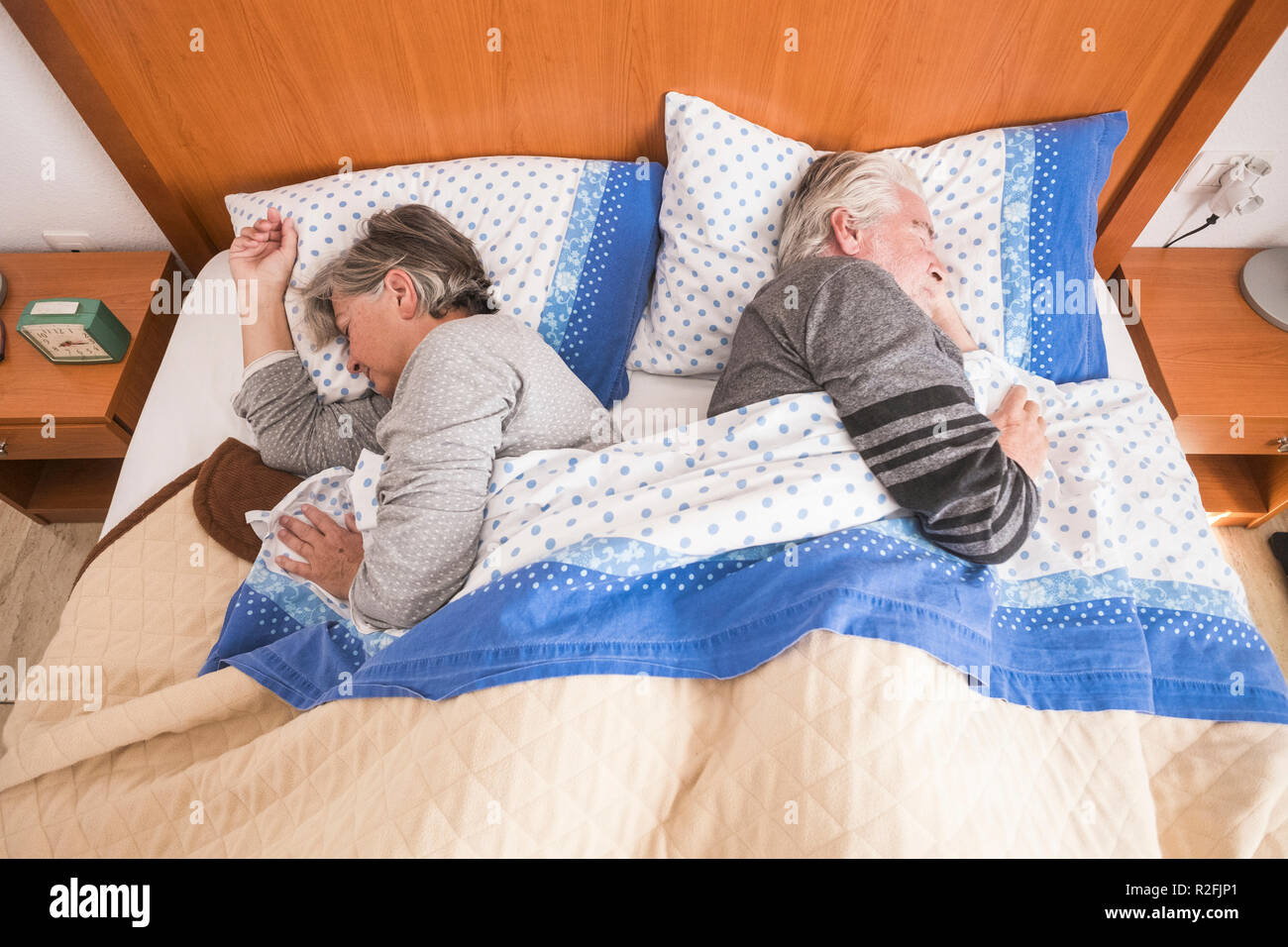 morning time wake up for adult senior couple at home in the bed. sleep together in the light from the window, day life concept. Stock Photo