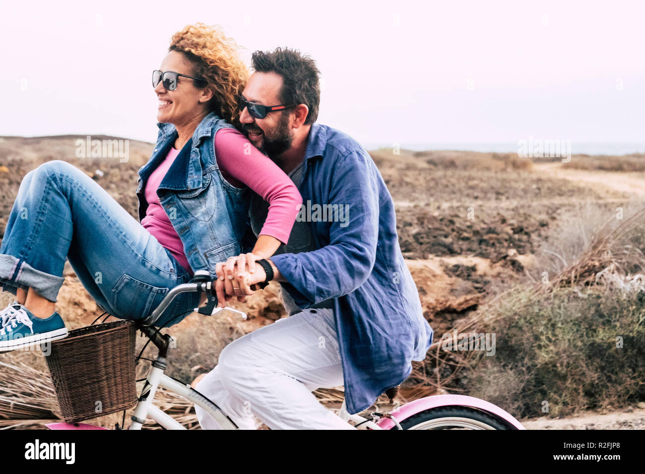 happy adult caucasian, couple having fun with bicycle in outdoor leisure activity. concept of active playful people with bike during vacation - everyday joy lifestyle withouth age limitation - man carry woman and both have fun and laugh a lot with wind in the air - Stock Image