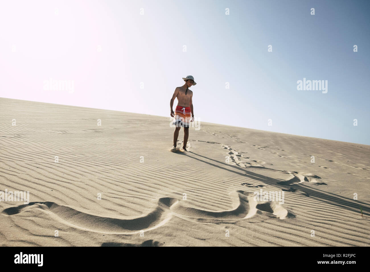 lost in happiness in the middle of the desert with sand dunes. young happy boy teenager enjoying vacation at the beach. clear blue sky in background. swimsuits and signs on the sand. summer day Stock Photo