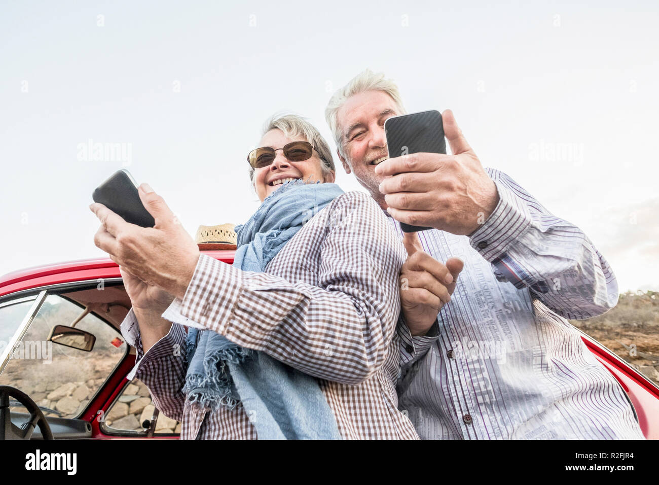 alternative point of view from the bottom for youthful senior couple caucasian people using smartphone to take pictures and connect to internet. travel and vacation summer time concept for happy people Stock Photo