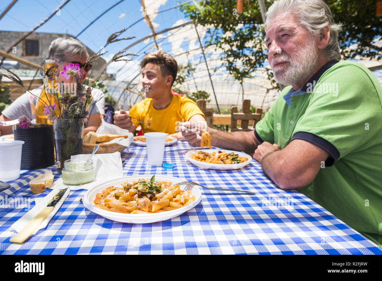 grandfathers and grandson together in an alternative biological nature concept restaurant with italian food pasta on the table having fun in friendship smiling and speaking. family at lunch in holiday concept - Stock Image